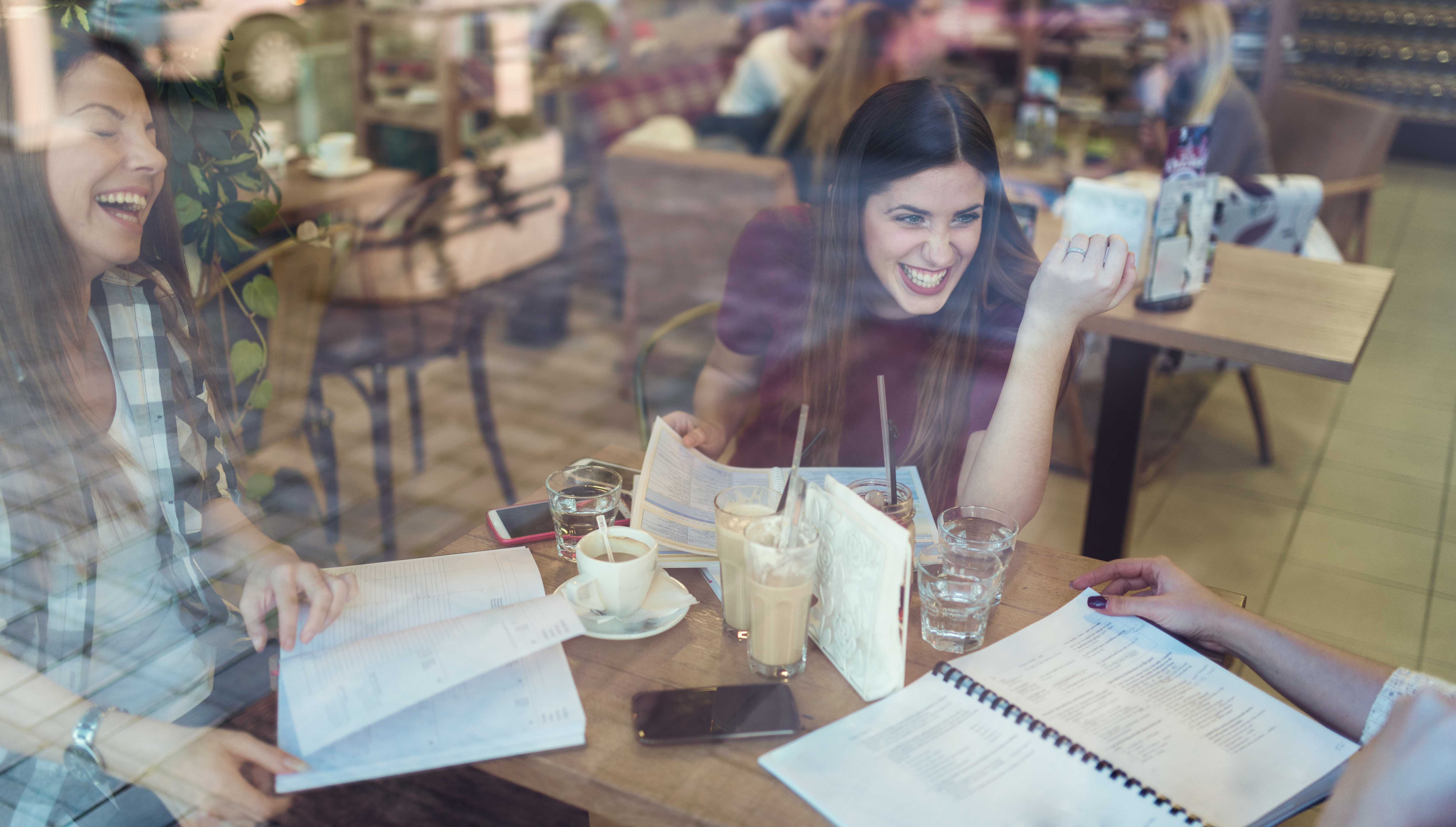 Smiling student girls talking in coffe shop after classes
