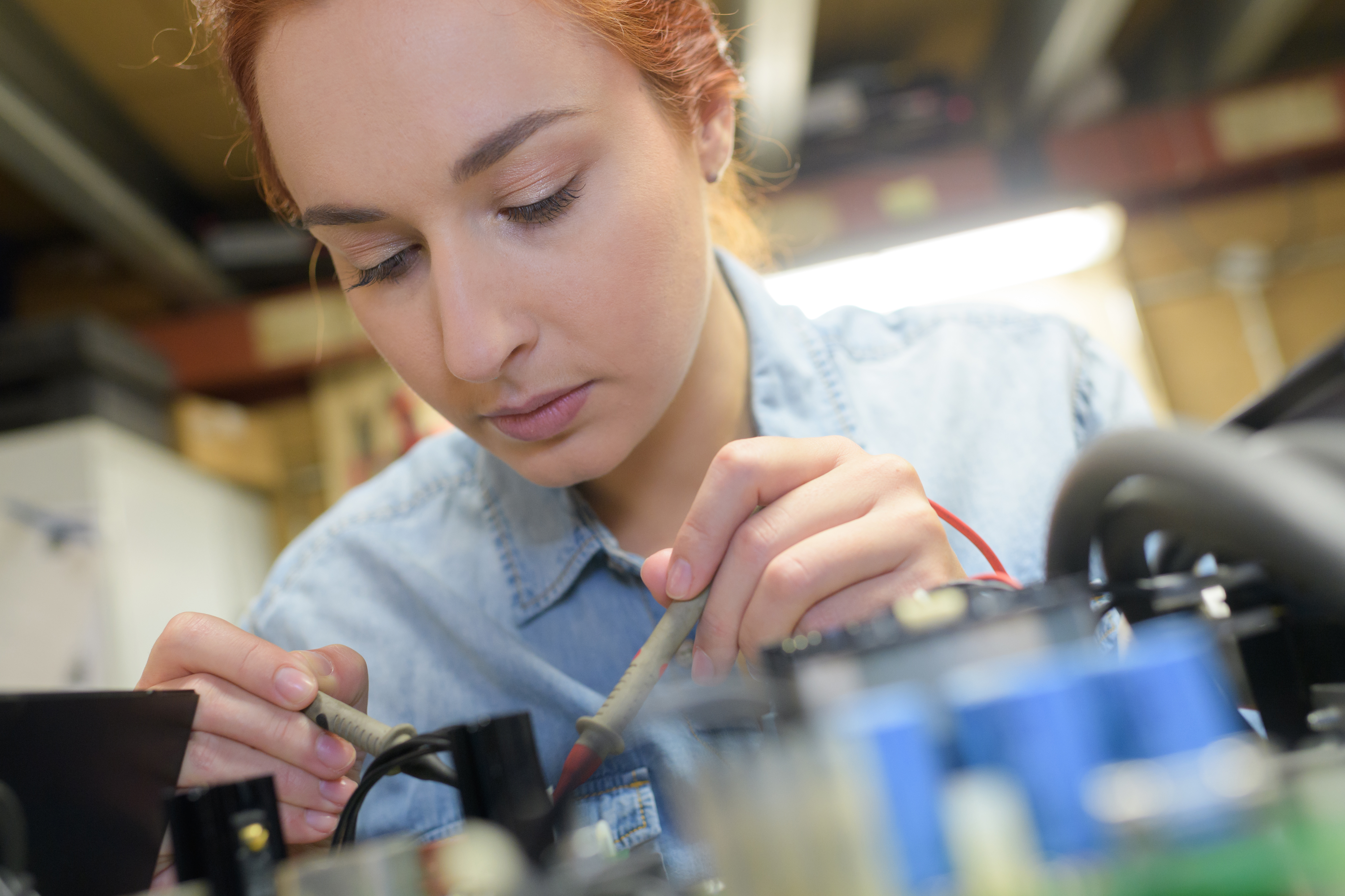 female tech fixes an electronic circuit
